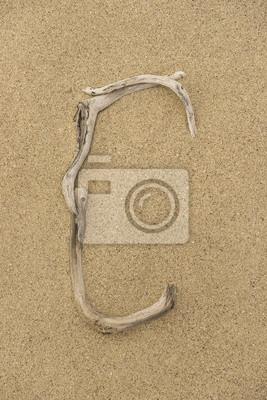 Alfabeto Letra C hecha de trozos de madera sobre la arena