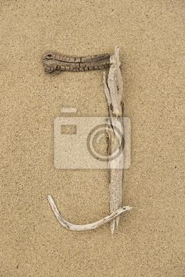 Alfabeto Letra J hecha de trozos de madera sobre la arena