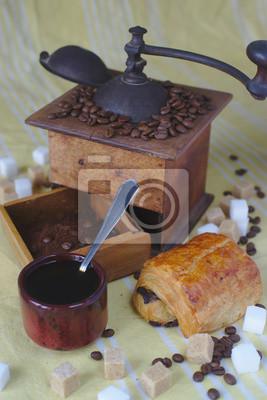 ancien moulin à café, cup, cuiller et cubes de sucre brun et blanc. Pain au chocolat