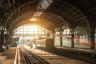 Cuadro Antigua estación de ferrocarril con un tren y una locomotora en el andén a la espera de la salida. Rayos de sol de la tarde en arcos de humo.