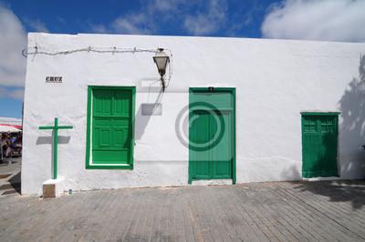 Antigua iglesia con puertas verdes en una pared blanca