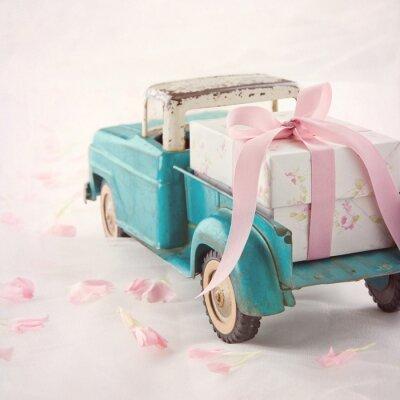 Cuadro Antiguo camión de juguete antiguo que lleva una caja de regalo con la cinta rosada