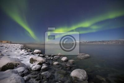 Aurora boreal sobre un fiordo iluminado por la luna en el norte de Noruega
