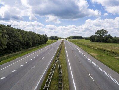 Autopista de cuatro carriles sin tráfico excepto en la distancia, en un día soleado