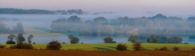 Autumn landscape. Fields, meadows and forest shrouded in morning mist.