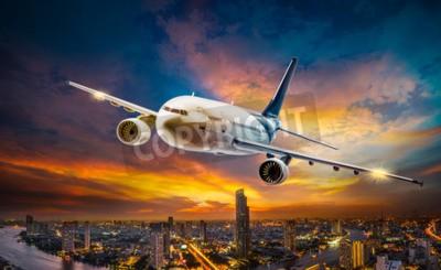 Cuadro Avión para el transporte que sobrevuela la ciudad de la escena de la noche en el fondo hermoso atardecer