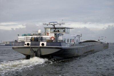 Barcaza de carga, visto en la parte posterior, navegando en un río