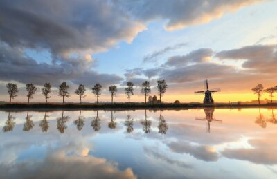beautiful sunrise over windmill and river on countryside