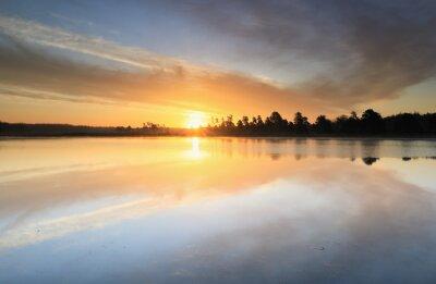 beautiful sunrise reflected in big forest lake