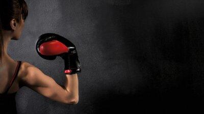 Cuadro Boxeador de la mujer con el bíceps guante de boxeo rojo sobre fondo negro, alto contraste con filtro de grunge saturado