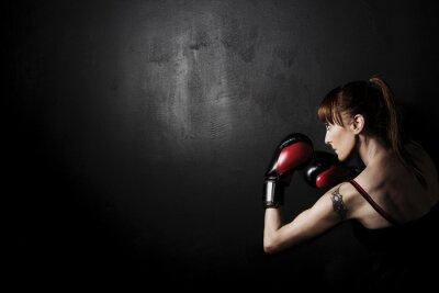 Cuadro Boxeador de la mujer con los guantes rojos en Fondo Negro, de alto contraste con filtro de grunge desaturado en el estudio