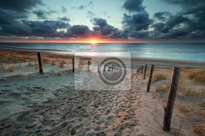 Camino de arena a la playa del mar del norte al atardecer