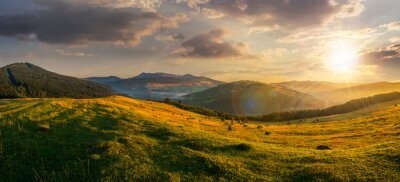 Cuadro campo agrícola en las montañas al atardecer