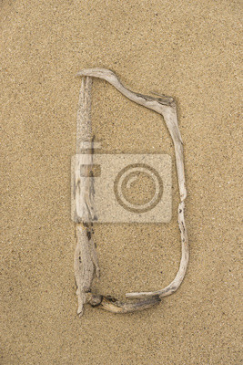 Carta del alfabeto D hecha de trozos de madera sobre la arena