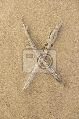 Carta del alfabeto X hecha de trozos de madera sobre la arena