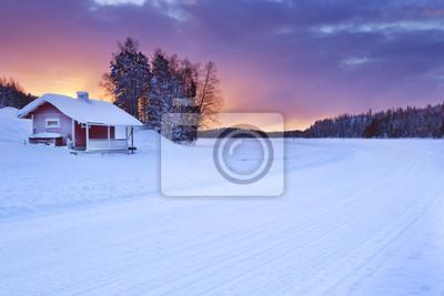 Casa de campo a lo largo de un lago congelado en invierno, Levi, Laponia finlandesa