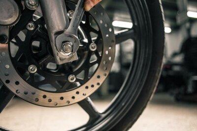 Cuadro Cerca de la mano del hombre que sostiene la llave de montaje cerca del vehículo de la motocicleta.