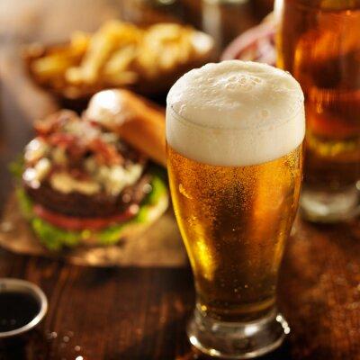 Cuadro cerveza con hamburguesas en mesa de restaurante
