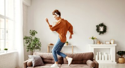 Cuadro Cheerful woman listening to music and dancing on soft couch at home in day off.