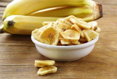 Cuadro Chips de plátano, frutos secos en una mesa de madera