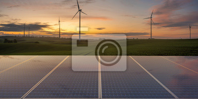 clean energy concept, photovoltaic panels and wind turbines in the light of the rising sun