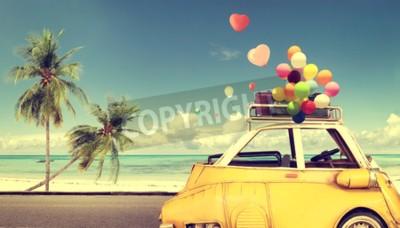 Cuadro Coche amarillo de la vendimia con el globo colorido del corazón en el cielo azul de la playa - concepto de amor en verano y boda. Luna de miel