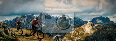 Cuadro Cycling outdoor adventure in Dolomites. Cycling woman and man  on electric mountain bikes in Dolomites landscape. Couple cycling MTB enduro trail track. Outdoor sport activity.