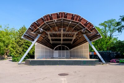 Deserted open air stage in a park with a sound projecting roof and no people on a sunny day