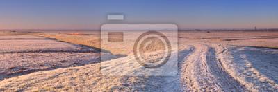 Dike through Dutch landscape in winter at sunrise