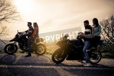 Cuadro Dos motos de conducción en la naturaleza - Amigos de conducción de motocicletas con sus amigas - Grupo de motociclistas de parada en un punto de vista panorámica y mirar la puesta de sol