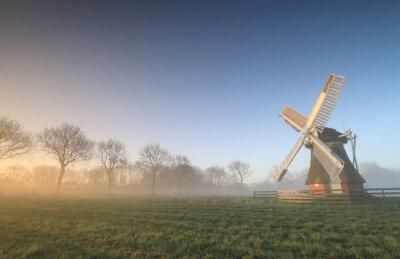 Dutch windmill in misty sunrise