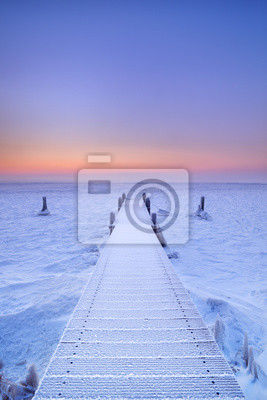 Embarcadero en un lago congelado en los Países Bajos al amanecer