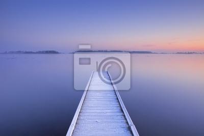 Embarcadero en un lago todavía en invierno en los Países Bajos