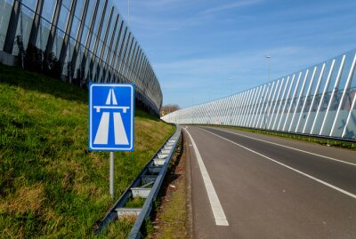Entry ramp of a highway, with traffic sign, sound screens and no traffic