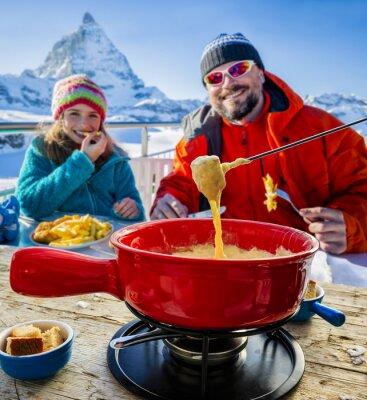Cuadro Esquiadores en un restaurante, fondue, plato suizo tradicional - Matterhorn en los Alpes suizos en el fondo