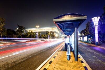 Cuadro estación de autobuses al lado de una carretera por la noche