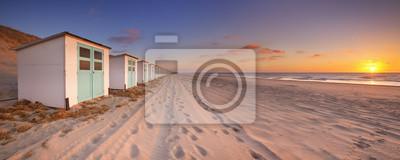 Fila de cabañas de playa al atardecer, isla de Texel, Países Bajos