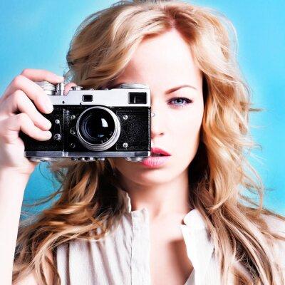 Cuadro fotógrafo hermosa mujer rubia que sostiene la cámara retro