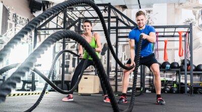 Cuadro Frau und Mann im Fitnessstudio con cuerda de batalla