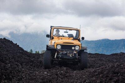 Cuadro Frontside vista de un conductor de pelo rizado en vehículo offroad amarillo estacionado en la parte superior de un valle con roca volcánica y montañas en Bali, Indonesia