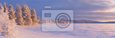 Frozen Äijäjärvi lake in Finnish Lapland in winter at sunset