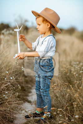 Full body portrait of a curious young boy playing with toy wind turbine in the field, studying how green energy works from a young age