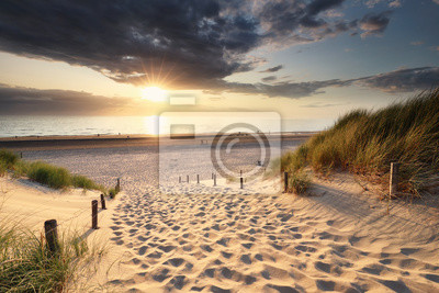 golden sunset light over sand path to North sea beach