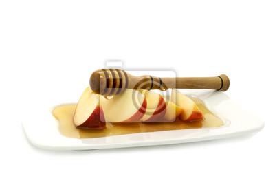 Goteo de la miel en las rebanadas de manzanas rojas aisladas en blanco