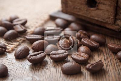Grains de café y toile de jutte sur table en bois avec ancien moulin à café décoratif