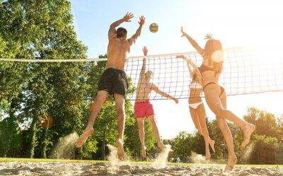 Cuadro Grupo Amigos jóvenes juegan a voleibol en la playa