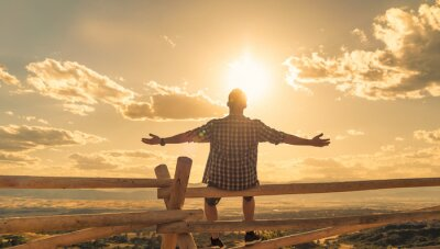 Cuadro Happy man sitting outdoors looking up to the sky with arms outstretched. People freedom and happiness concept.