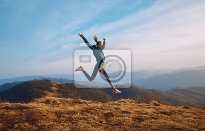 Cuadro Happy woman hiker jumping on mountain ridge on blue cloudy sky and mountains background. Travel and active lifestyle concept.