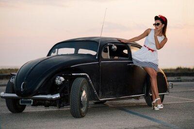 Cuadro Hermosa chica pin-up que presenta con el coche de carretera caliente