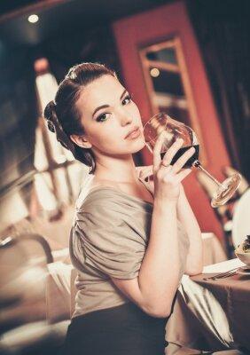 Cuadro Hermosa joven con el vidrio de rojo winein un restaurante